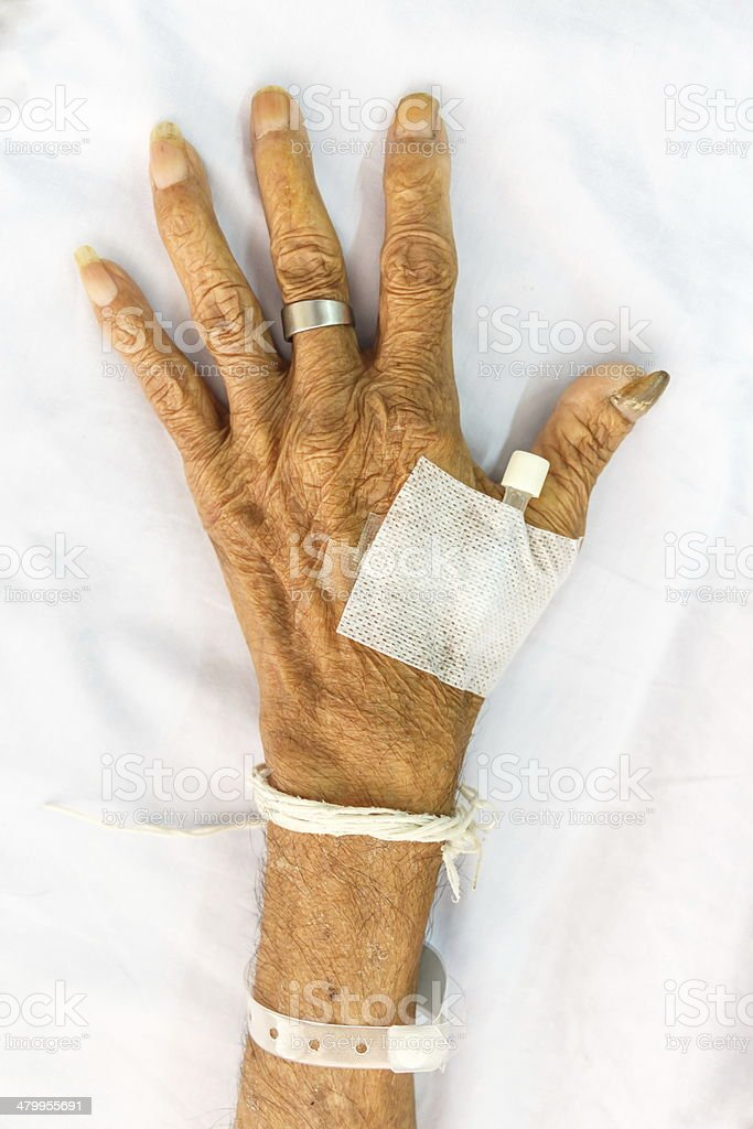 hand of old patient with plug on bed in hospital stock photo