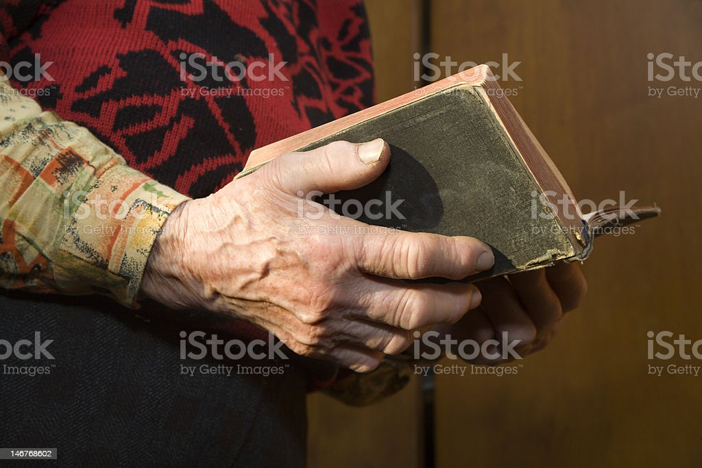 hand of old woman by prayer stock photo