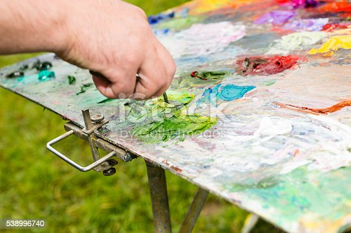 504223972istockphoto Hand of painter mixing colors on a palette outdoors 538996740