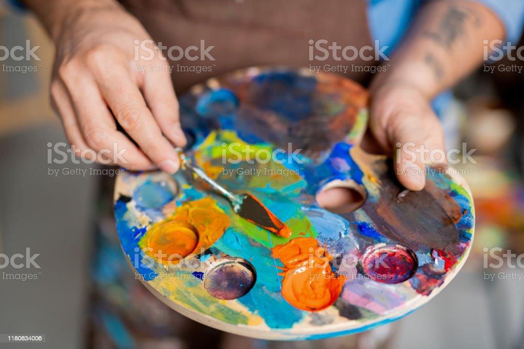 Hand des Malers Mischen von Farben auf Palette mit kleinem Instrument vor dem Malen - Lizenzfrei Acrylmalerei Stock-Foto