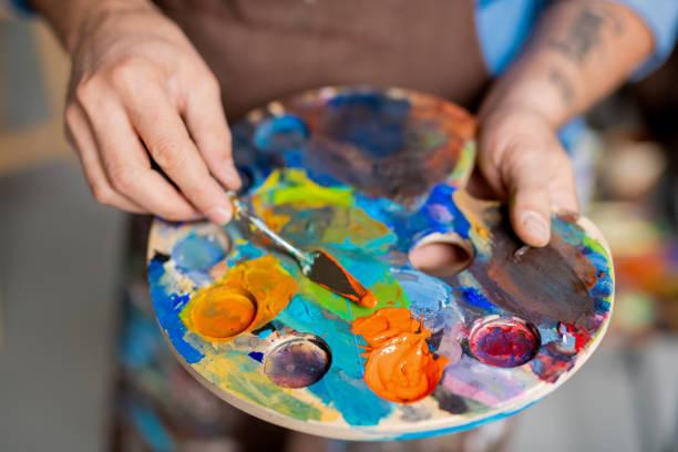 Hand des Malers Mischen von Farben auf Palette mit kleinem Instrument vor dem Malen – Foto