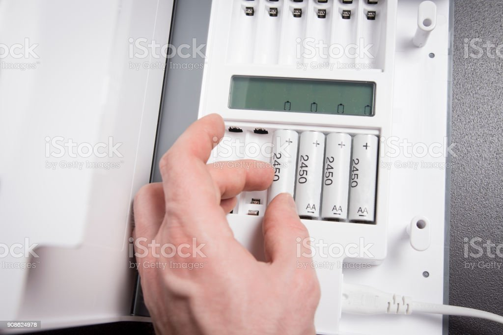 hand of person recharges rechargeable batteries close-up. Battery charging device. Charge accumulators. stock photo