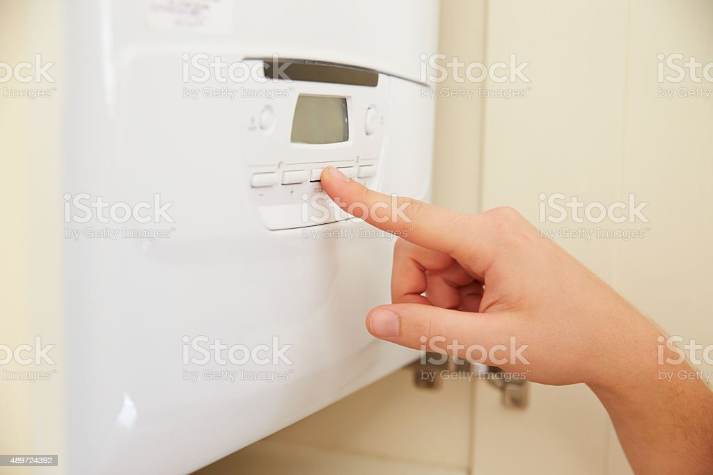 Hand of person using domestic boiler controls, close up stock photo