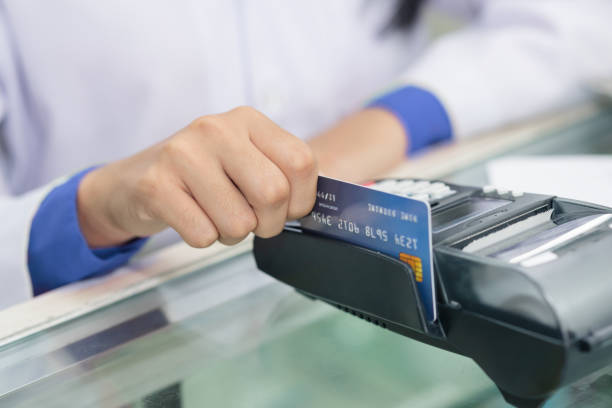 Hand of  pharmacist, chemist making purchases, Paying with a credit card Hand of  pharmacist, chemist making purchases, Paying with a credit card and using a terminal on many medicines shelf in pharmacy background. smart card stock pictures, royalty-free photos & images