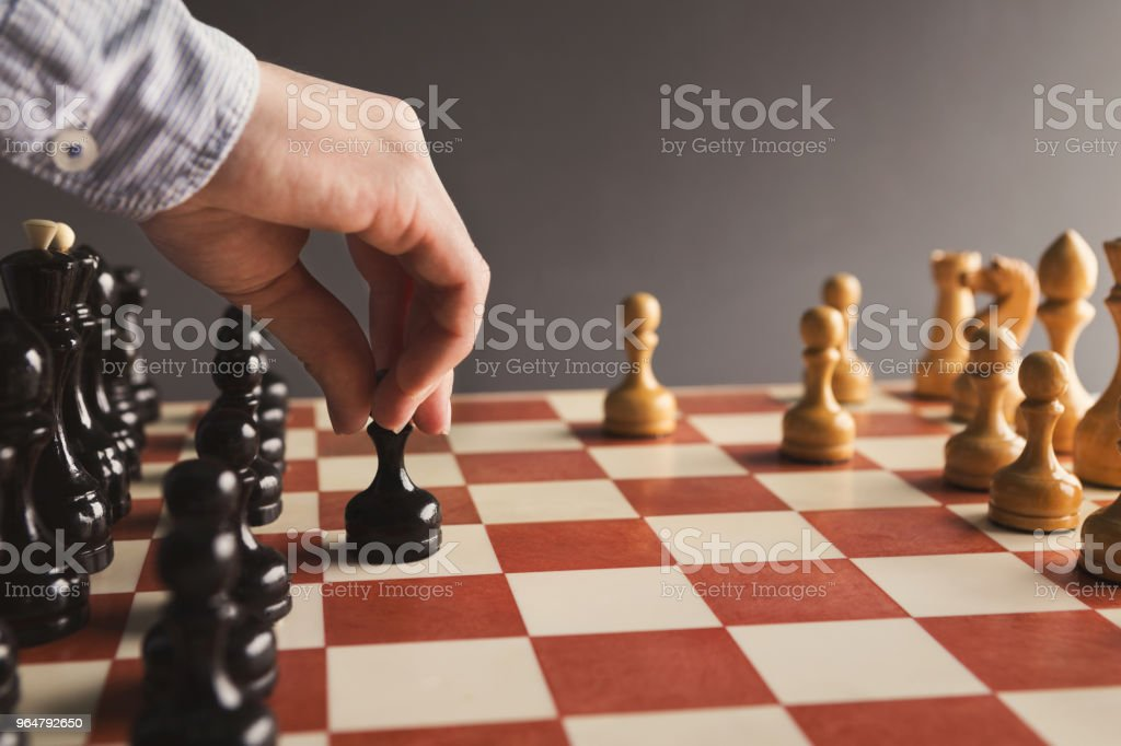 Hand of player chess board game putting black pawn royalty-free stock photo