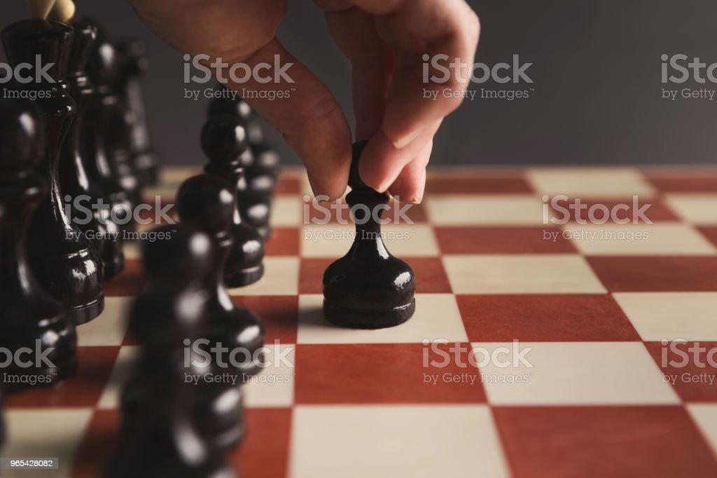 Mão do jogo de tabuleiro de xadrez jogador colocando o peão preto - Foto de stock de Atitude royalty-free