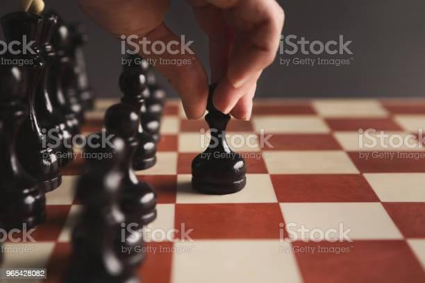 Foto de Mão Do Jogo De Tabuleiro De Xadrez Jogador Colocando O Peão Preto e mais fotos de stock de Atitude