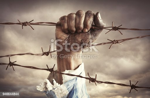 Hand of refugee holding barbed wire