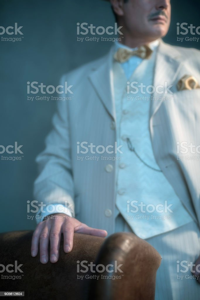 Hand of retro 1920s business man on backrest of leather chair. stock photo