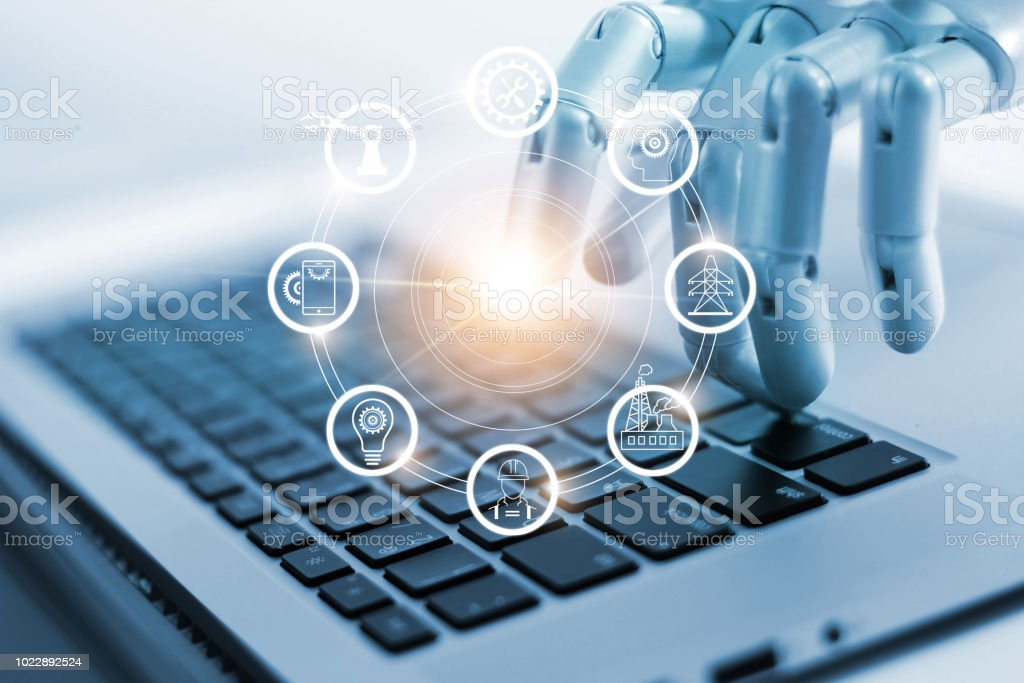 Hand of robotics connecting to industrial network connection on laptop. Artificial intelligence. Futuristic technology and manufacturing concept. Hand of robotics connecting to industrial network connection on laptop. Artificial intelligence. Futuristic technology and manufacturing concept. Artificial Stock Photo