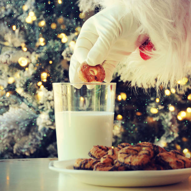 Hand of santa claus picking cookie on the table at home stock photo
