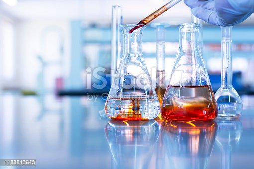 hand of scientist drop orange solution by pipette in glass flask in chemistry science laboratory blue background