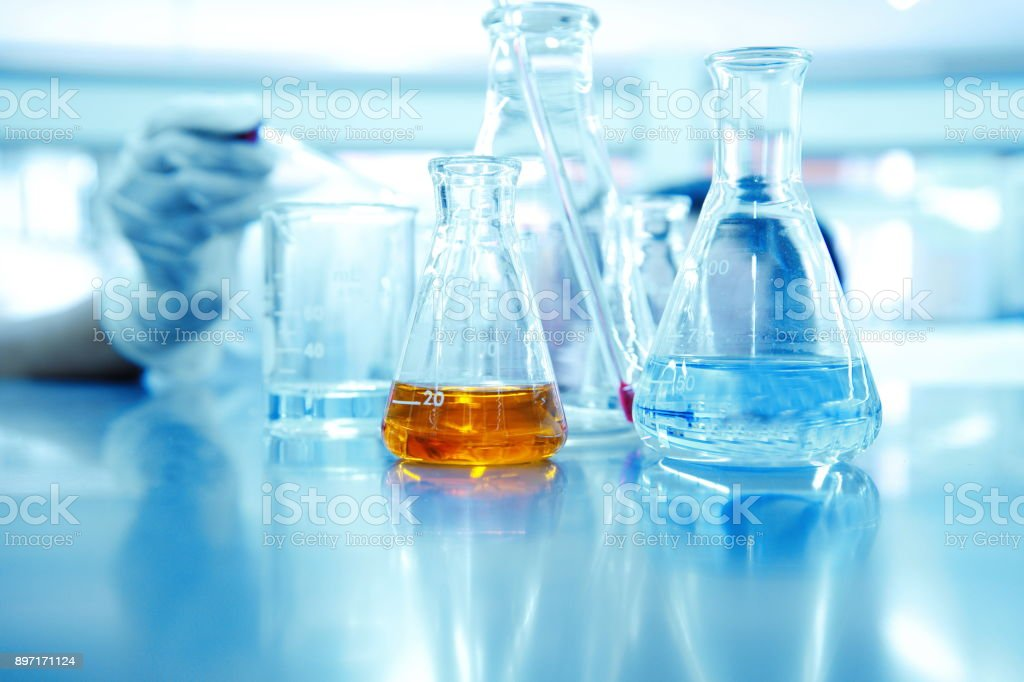 hand of scientist or reseracher drop solution in glass beaker and orange liquid in  flask at chemical science laboratory background stock photo