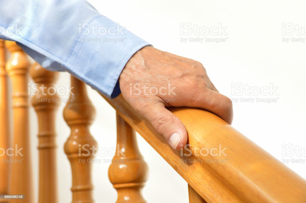 hand of senior man over a wooden railing stock photo