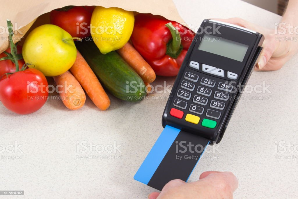 Hand of senior woman using payment terminal with credit card, cashless paying for shopping stock photo