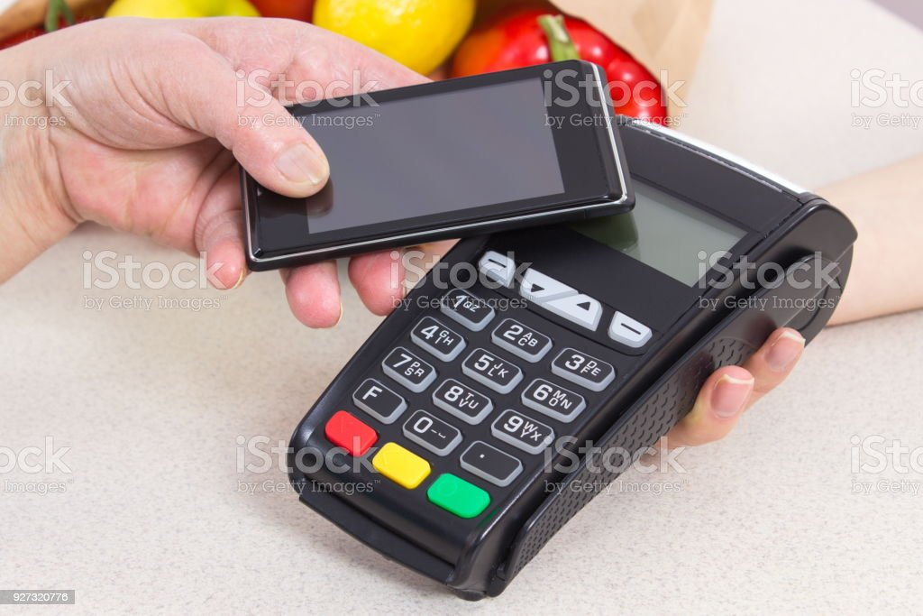Hand of senior woman using payment terminal with mobile phone, paying for shopping stock photo