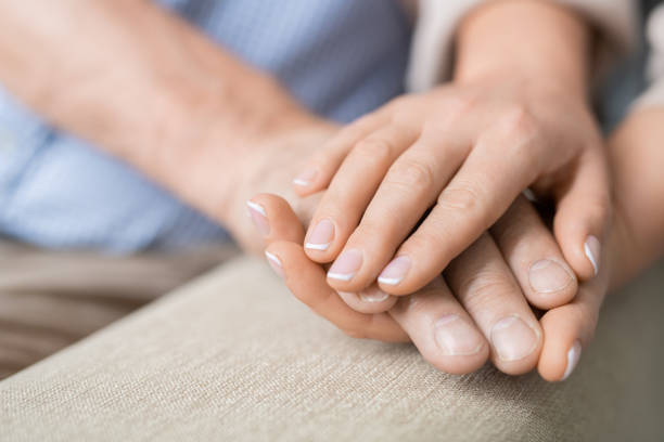 Hand of sick retired man between those of his careful young loving daughter stock photo