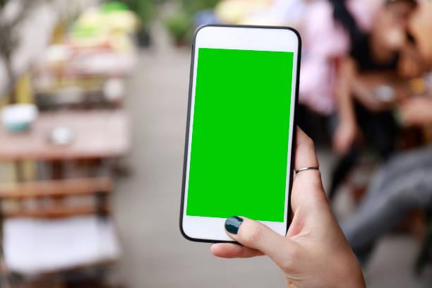 hand van smart woman holding en touch mobiele smart phone met chroma key groen scherm op de achtergrond van de stad - green screen stockfoto's en -beelden