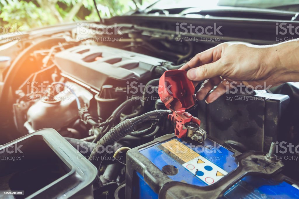 Hand of technician checking battery terminals and engine on the car. stock photo