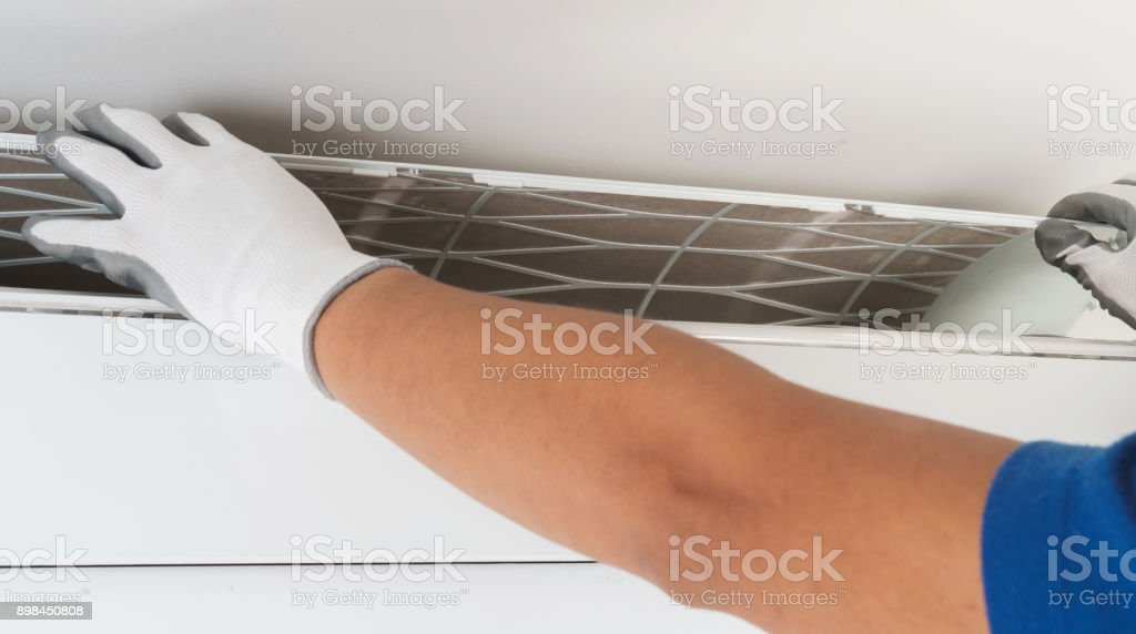 Hand of technician cleaning air conditioner in house stock photo