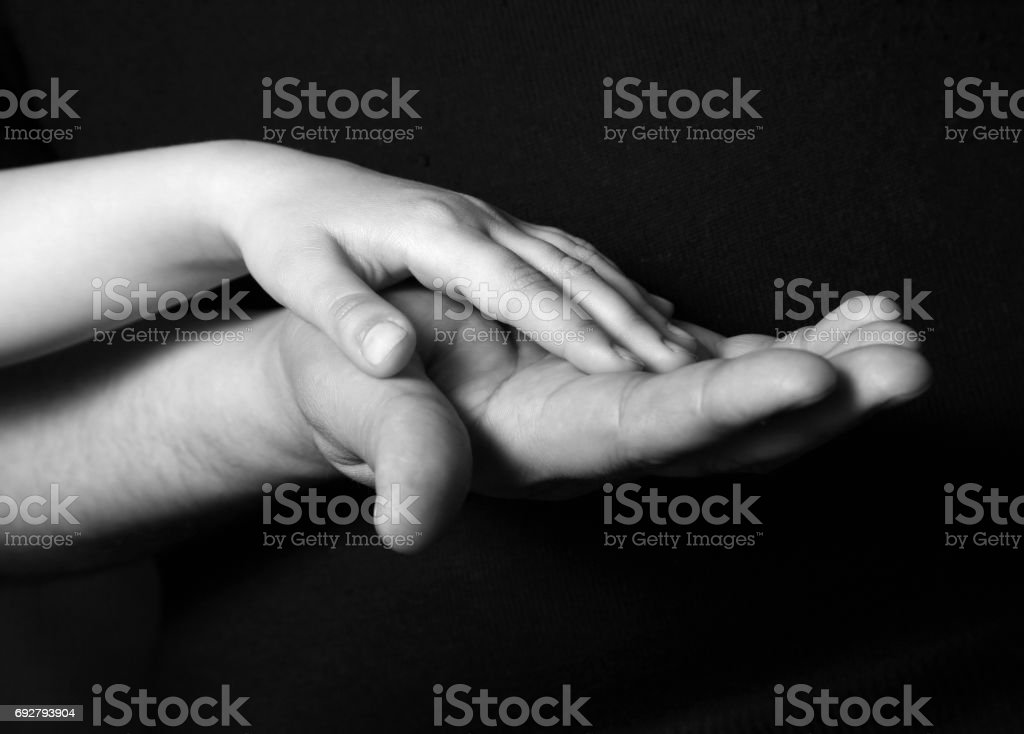 Hand Of The Adult Person And Hand Of The Small Child On A Dark Background Stock Photo Download Image Now Istock
