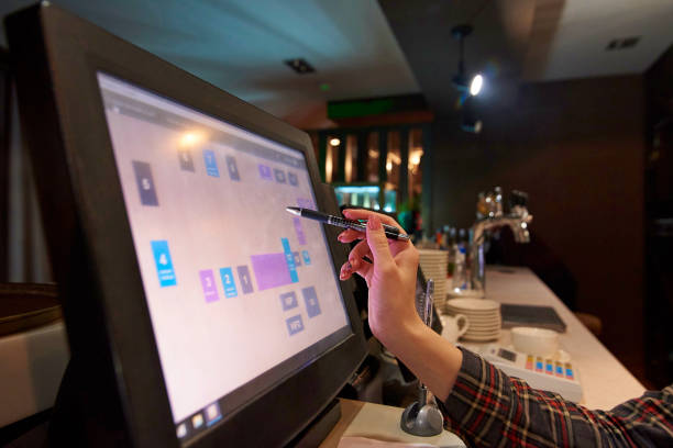 Hand of the waiter holds a fountain pen near the working touch screen monitor. stock photo