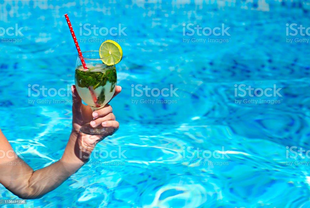c2c8d73e Mano de la mujer sosteniendo un vaso de mojito en la piscina foto de stock  libre