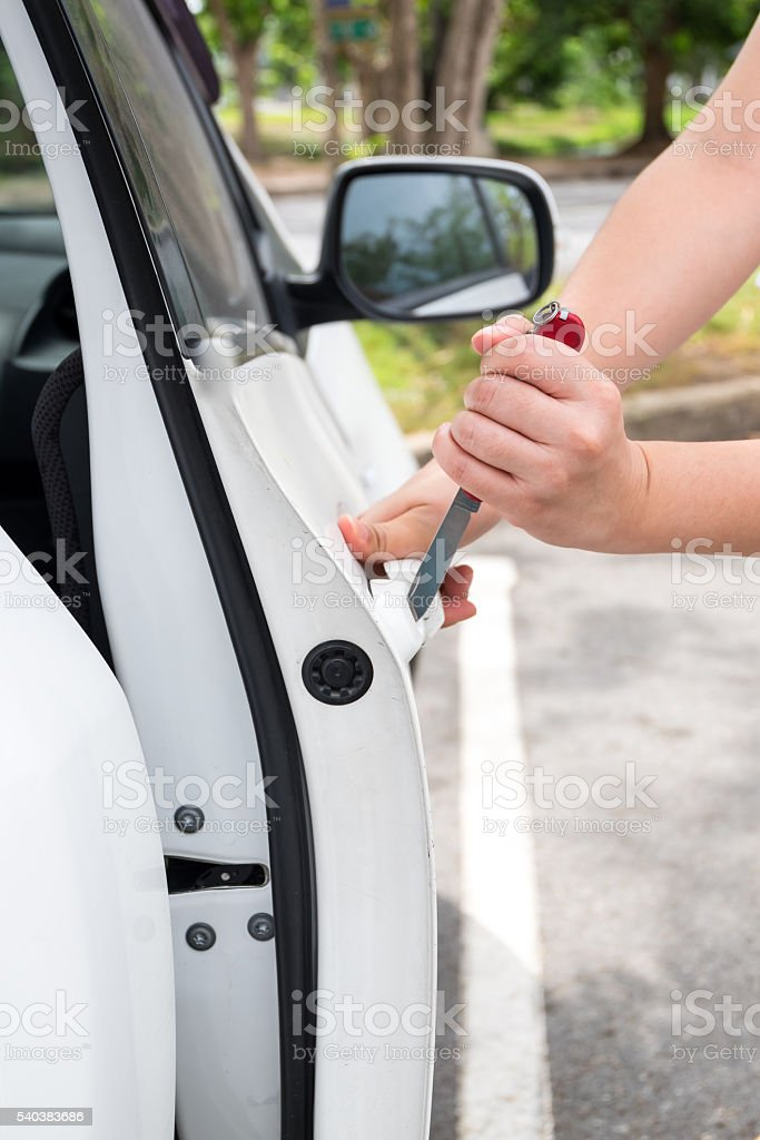 Hand of Thief using knife try to opening Car's Door stock photo