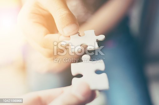 istock Hand of two people holding jigsaw puzzle connecting together. Concept of partnership and teamwork in business strategy 1042156966