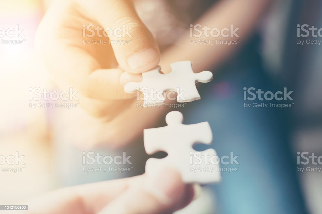 Hand of two people holding jigsaw puzzle connecting together. Concept of partnership and teamwork in business strategy stock photo