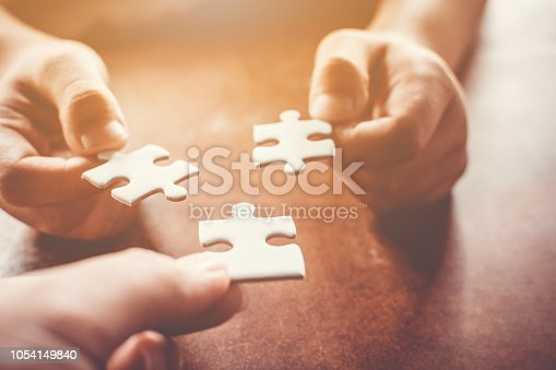 istock Hand of two people holding jigsaw puzzle connecting together. Concept of partnership and teamwork in business strategy 1054149840
