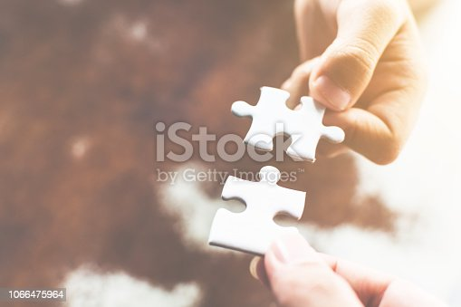 istock Hand of two people holding jigsaw puzzle connecting together. Concept of partnership and teamwork in business strategy 1066475964