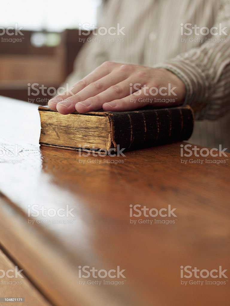 Hand of witness on Bible in courtroom stock photo