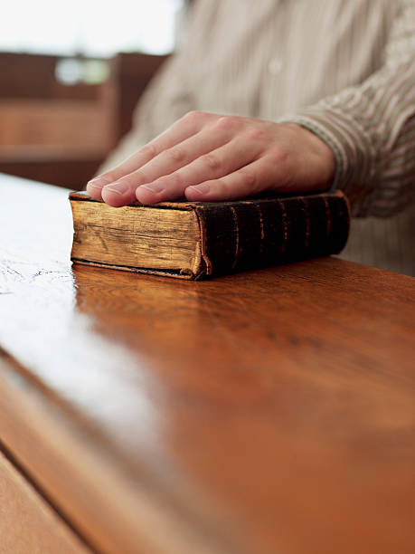 hand of witness on bible in courtroom - swearing stockfoto's en -beelden