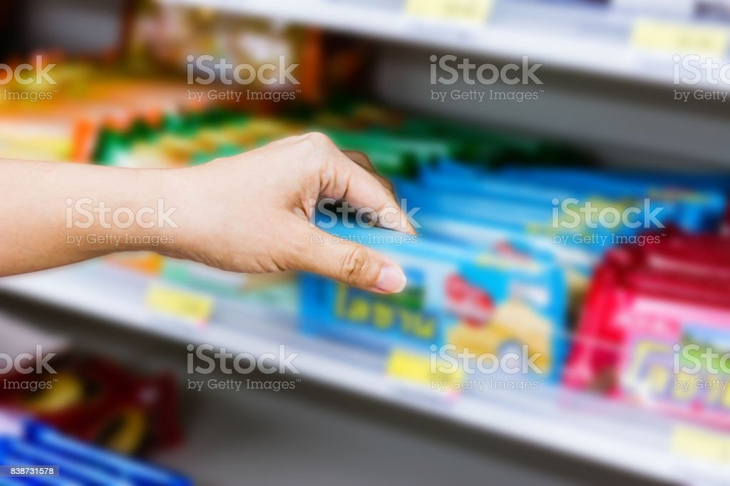 hand of woman choosing or taking sweet products, snacks on shelves in convenience store stock photo