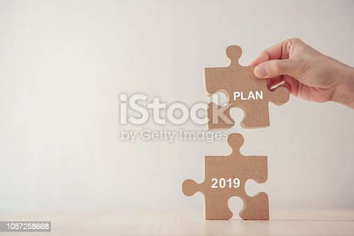 888342518istockphoto Hand of woman connecting jigsaw puzzle with new year planning 2019 1057258668
