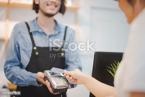 Hand of woman customer using wireless or contactless payment of a credit card. Young Asian cashier or seller are smiling to accept payment by nfc technology at retail shop. Contactless payment concept.