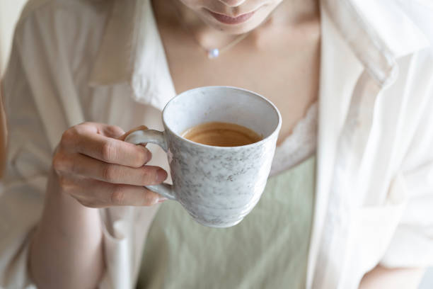 Hand of woman drinking coffee stock photo
