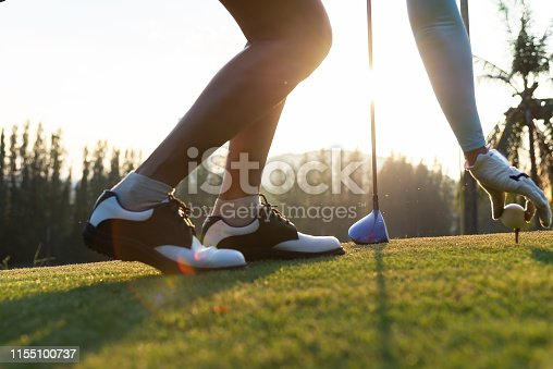 istock hand of woman golf player gentle put a golf ball onto wooden tee on the tee off, to make ready hit away from tee off to the fairway ahead. Healthy and Lifestyle Concept. 1155100737