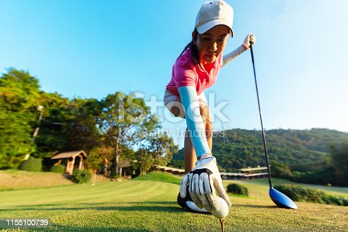 istock hand of woman golf player gentle put a golf ball onto wooden tee on the tee off, to make ready hit away from tee off to the fairway ahead. Healthy and Lifestyle Concept. 1155100739