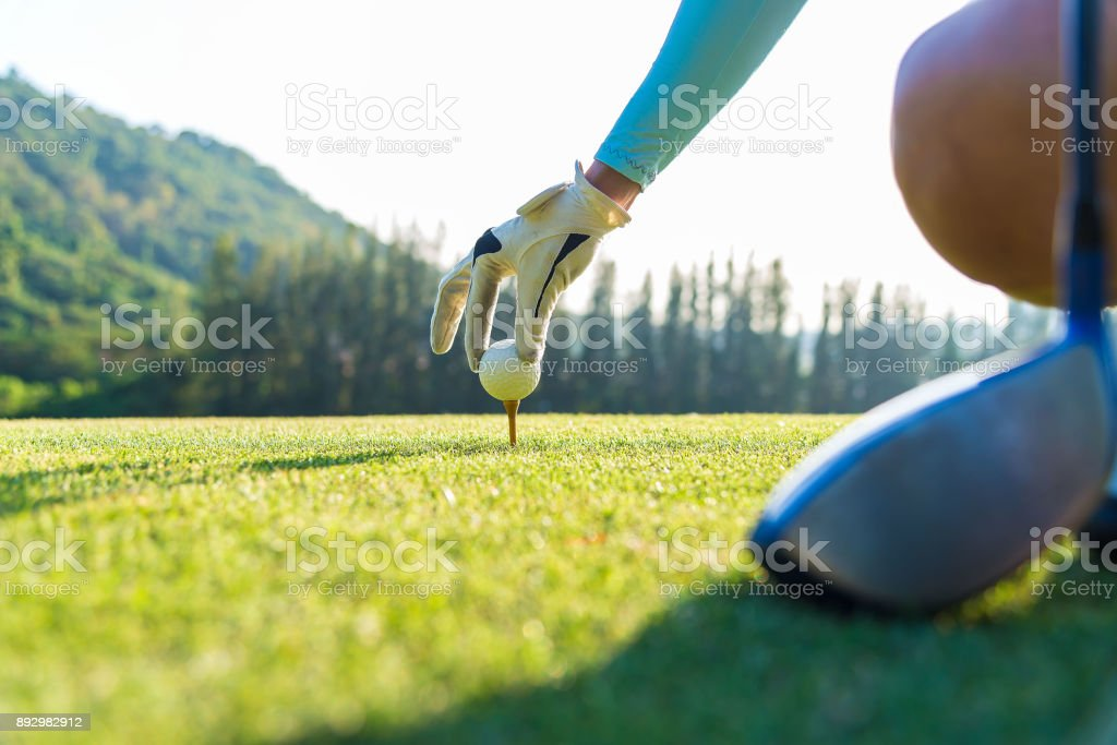 hand of woman golf player gentle put a golf ball onto wooden tee on the tee off, to make ready hit away from tee off to the fairway ahead stock photo