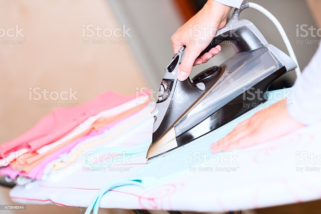 hand of woman ironing clothes angled stock photo