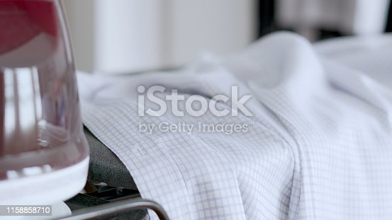 524159504 istock photo Hand of woman ironing clothes on the table 1158858710