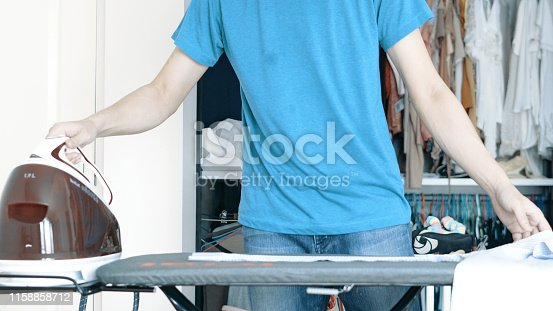 524159504 istock photo Hand of woman ironing clothes on the table 1158858712