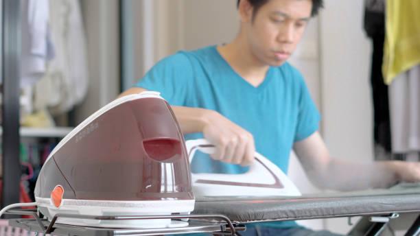 Hand der Frau Bügeln Kleidung auf dem Tisch – Foto