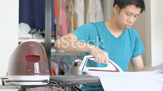 524159504 istock photo Hand of woman ironing clothes on the table 1158858734