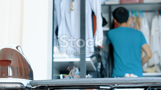 524159504 istock photo Hand of woman ironing clothes on the table 1158858735