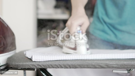 524159504 istock photo Hand of woman ironing clothes on the table 1158858738