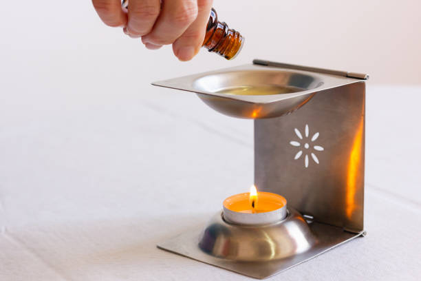 Hand of woman pouring essential oil into silver diffuser with candle underneath over white background stock photo