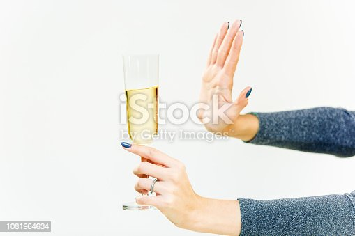 Hand of woman refusing glass with alcoholic beverage, on white background. No alcohol concept